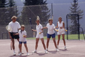 Group of people practising tennis with coach