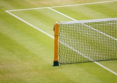 Detail of a tennis net and post on a grass court